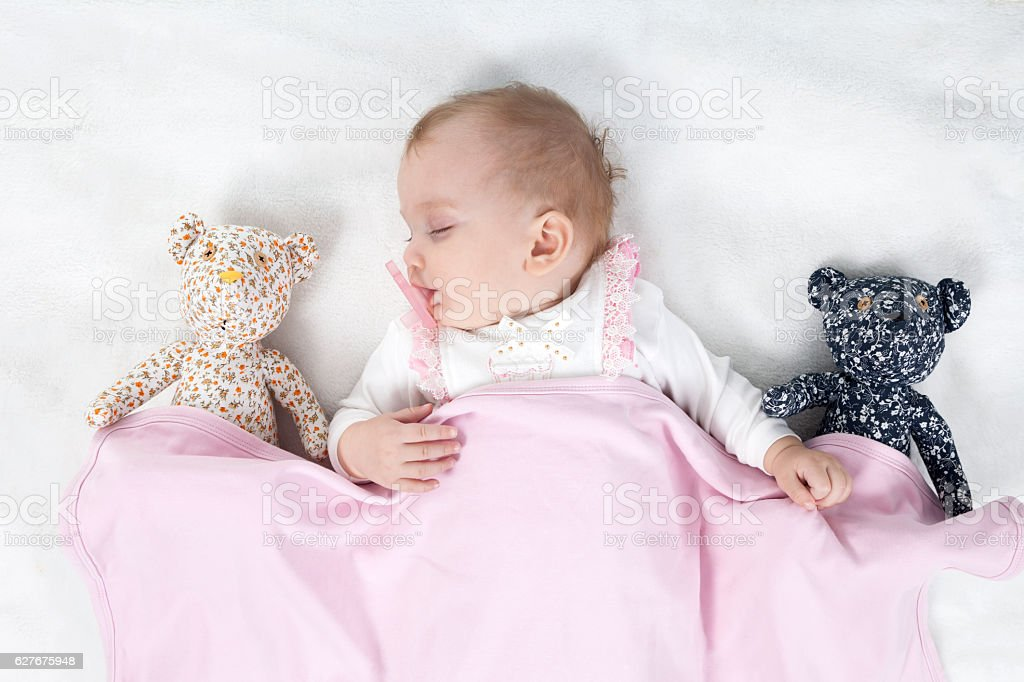 Baby girl sleeping with teddy bear stock photo