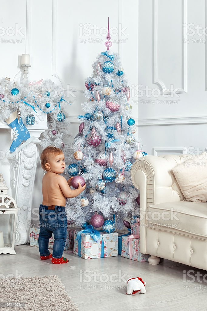 Baby girl standing near the Christmas tree stock photo