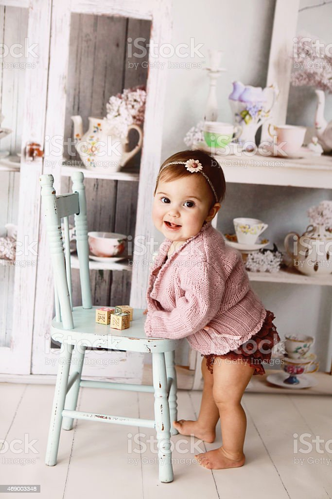 Baby girl standing while holding a blue wooden chair stock photo