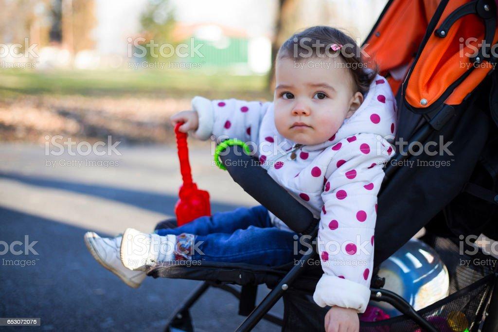Baby girl - toddler in stroller stock photo