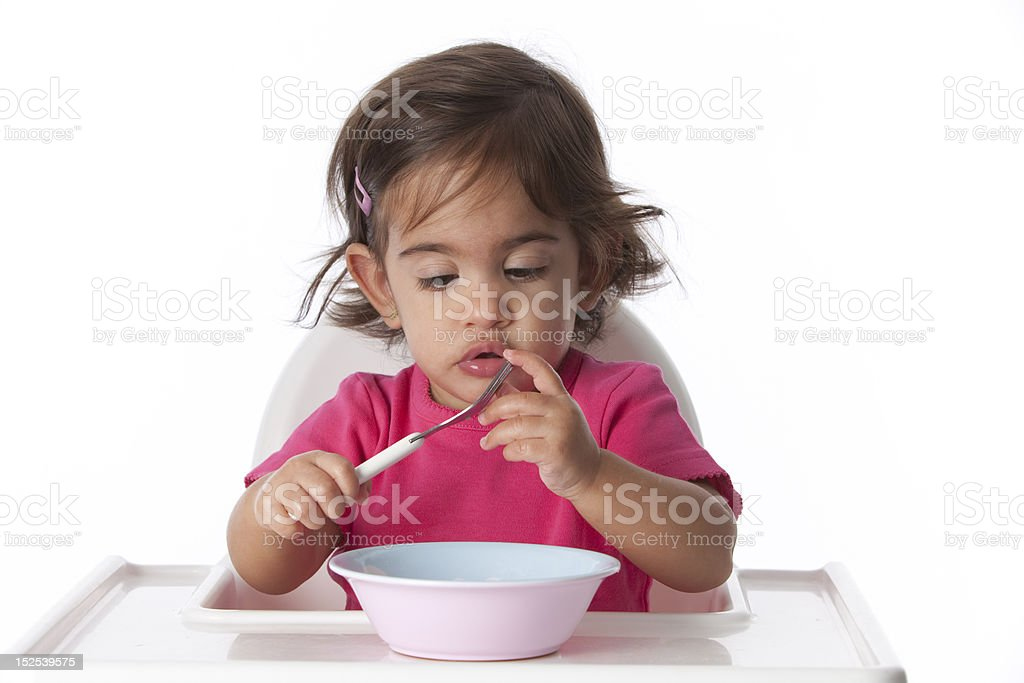 Baby girl touches her fork royalty-free stock photo
