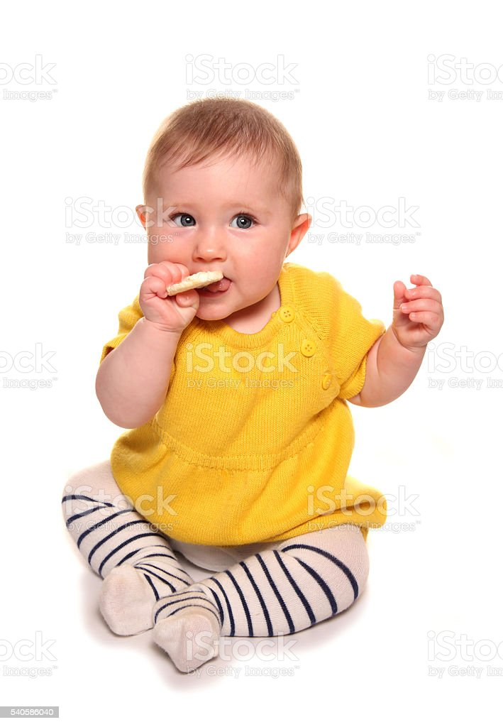 Baby girl trying a rice cake stock photo