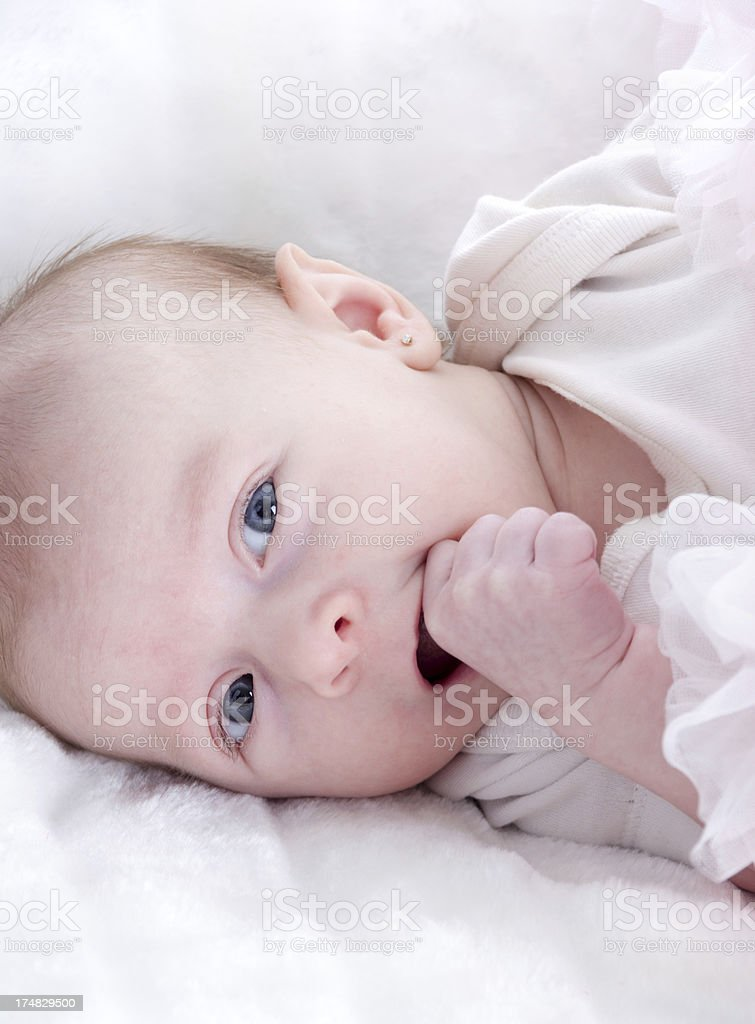 Baby girl trying to get fist in mouth. royalty-free stock photo