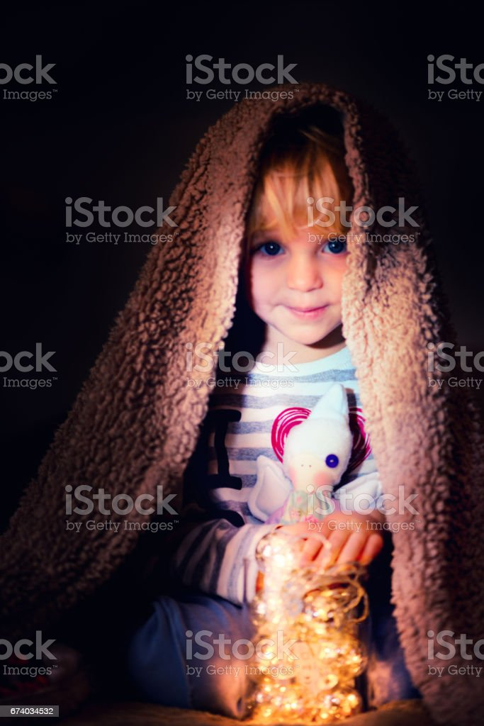 Baby Girl under the Blanket holding a Toy Angel stock photo