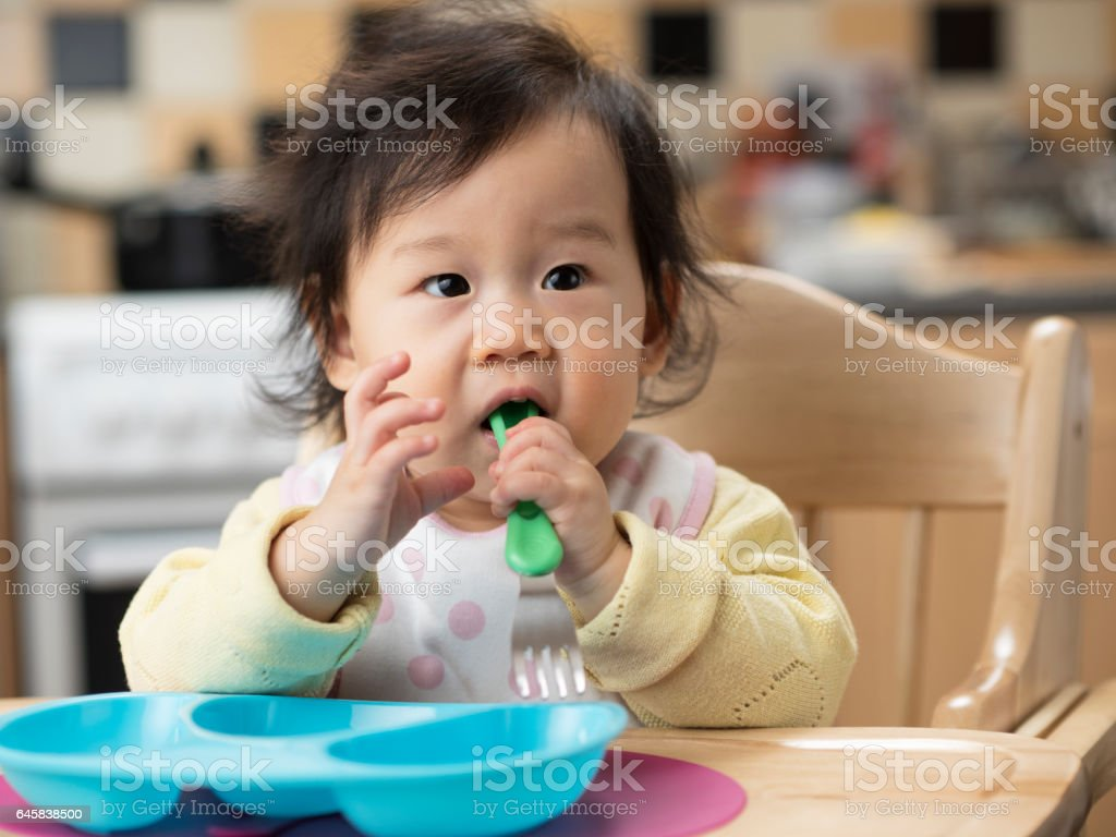 baby girl using spoon first time stock photo