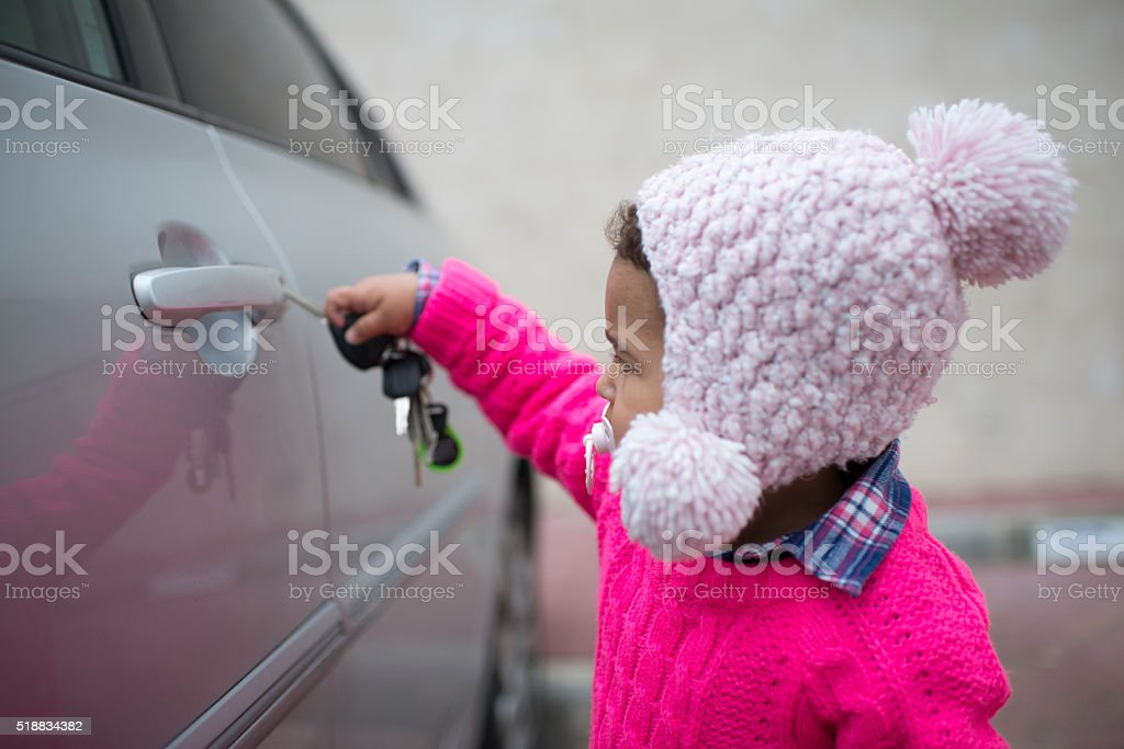Baby girl using the key to open a family car. stock photo