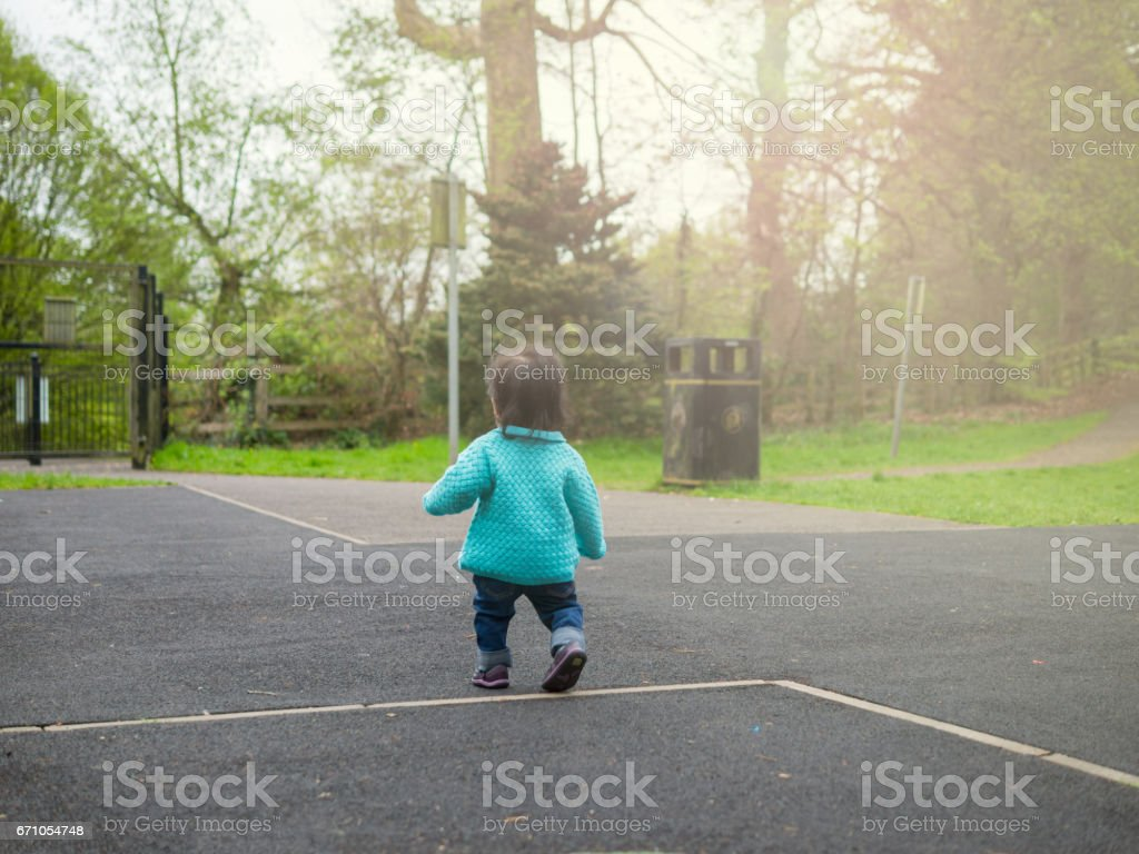 baby girl walking in the playground stock photo