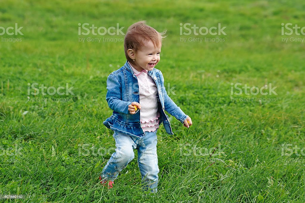 Baby girl walking on the grass stock photo