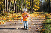 Baby girl walking smiling in the autumn park