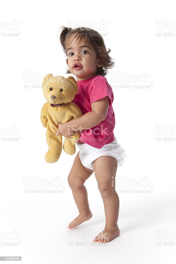Baby girl walking with a toy bear royalty-free stock photo