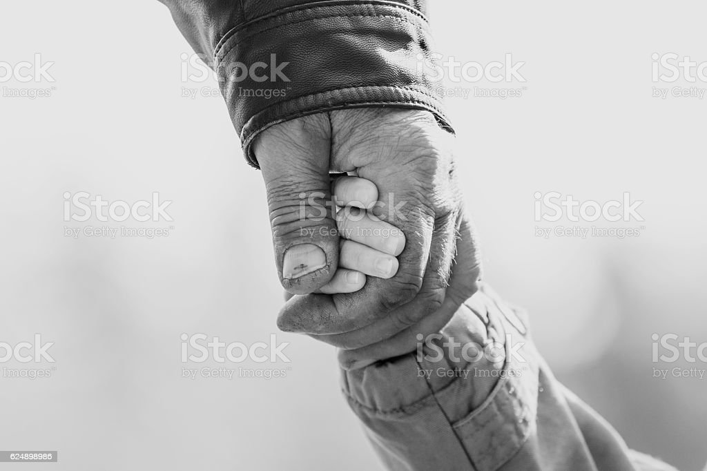 Baby girl warm jacket and cap c grandfather hands in stock photo
