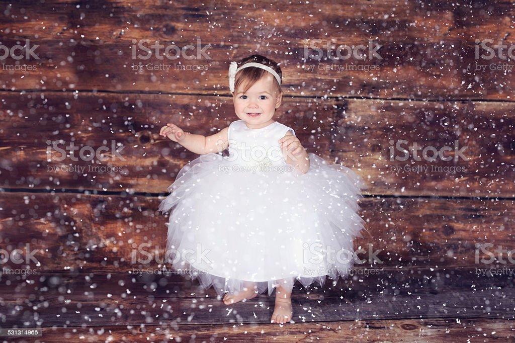 Baby girl wearing a white dress stock photo