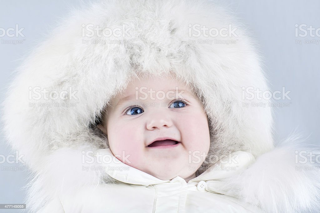 Baby girl wearing big fur hat and white winter jacket royalty-free stock photo