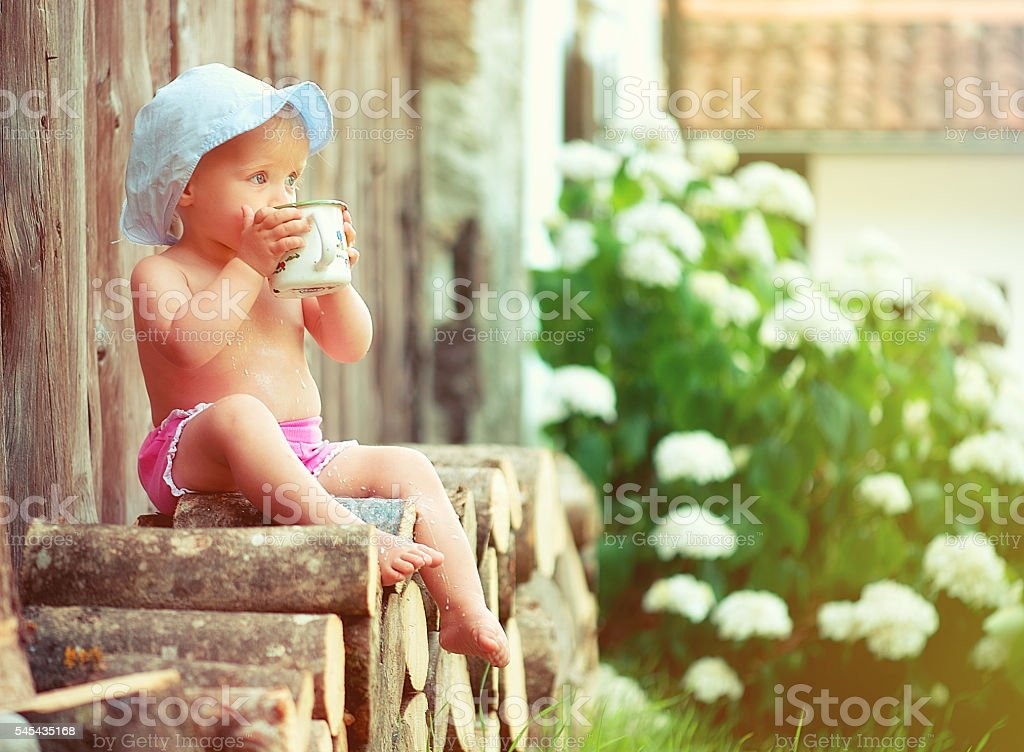 Baby girl with a big metal cup stock photo