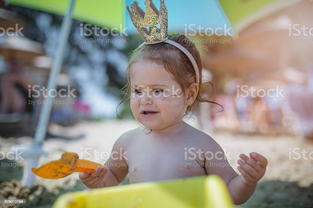 baby girl with a crown on a beach playing stock photo