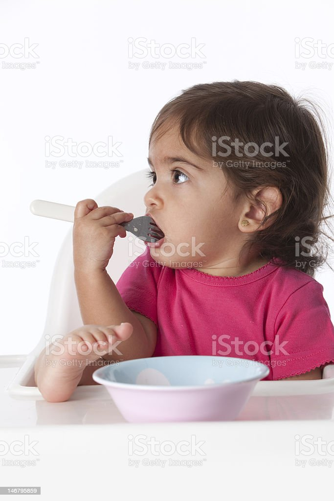 Baby girl with a fork in her mouth royalty-free stock photo