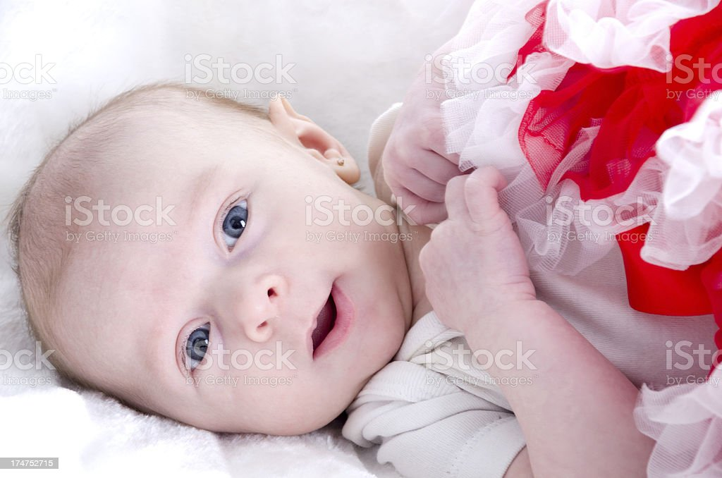 Baby girl with big smile on white fake fur. royalty-free stock photo