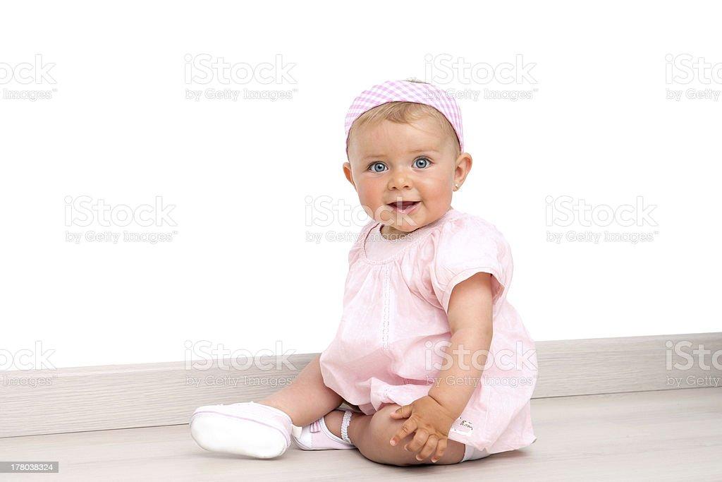 Bébé fille avec yeux bleus assis sur le sol photo libre de droits