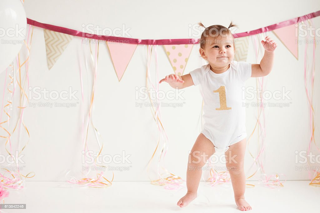 Baby girl's first birthday and first steps stock photo