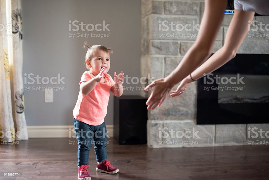 Baby girl's first step with her mother stock photo