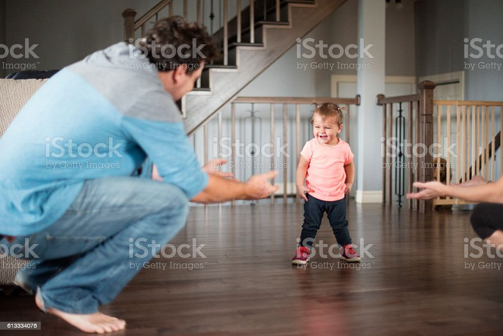 Baby girl's first steps with her parents stock photo