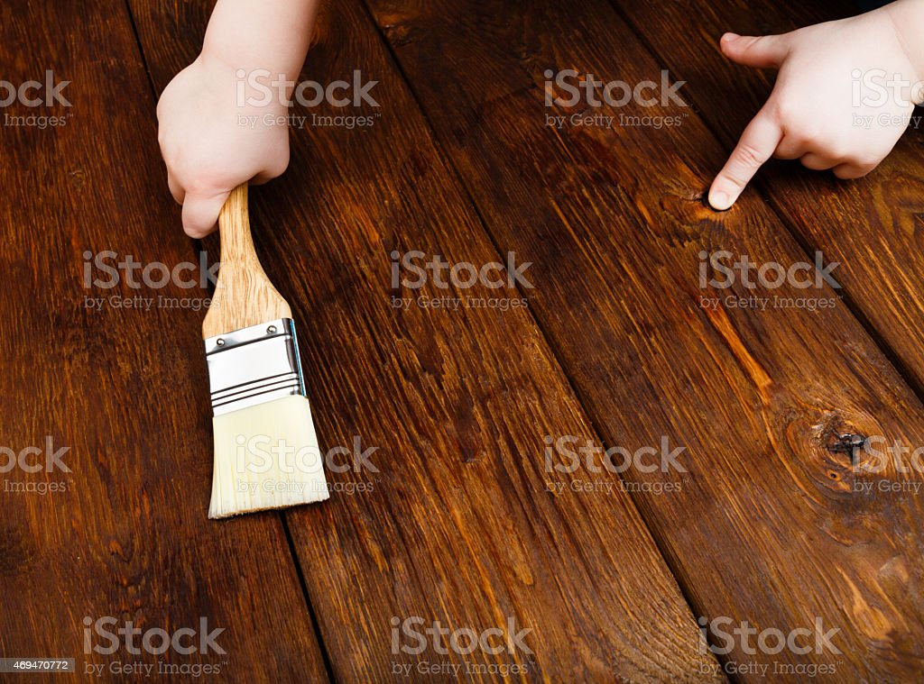 Baby hand applying protective varnish on a wooden table stock photo