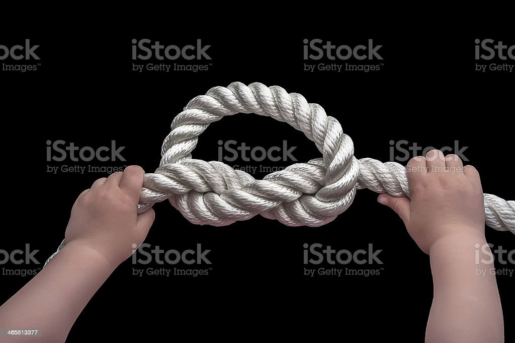 Baby hands holding overhand knot stock photo