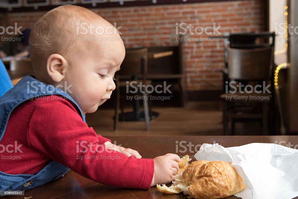Baby having a croisant stock photo