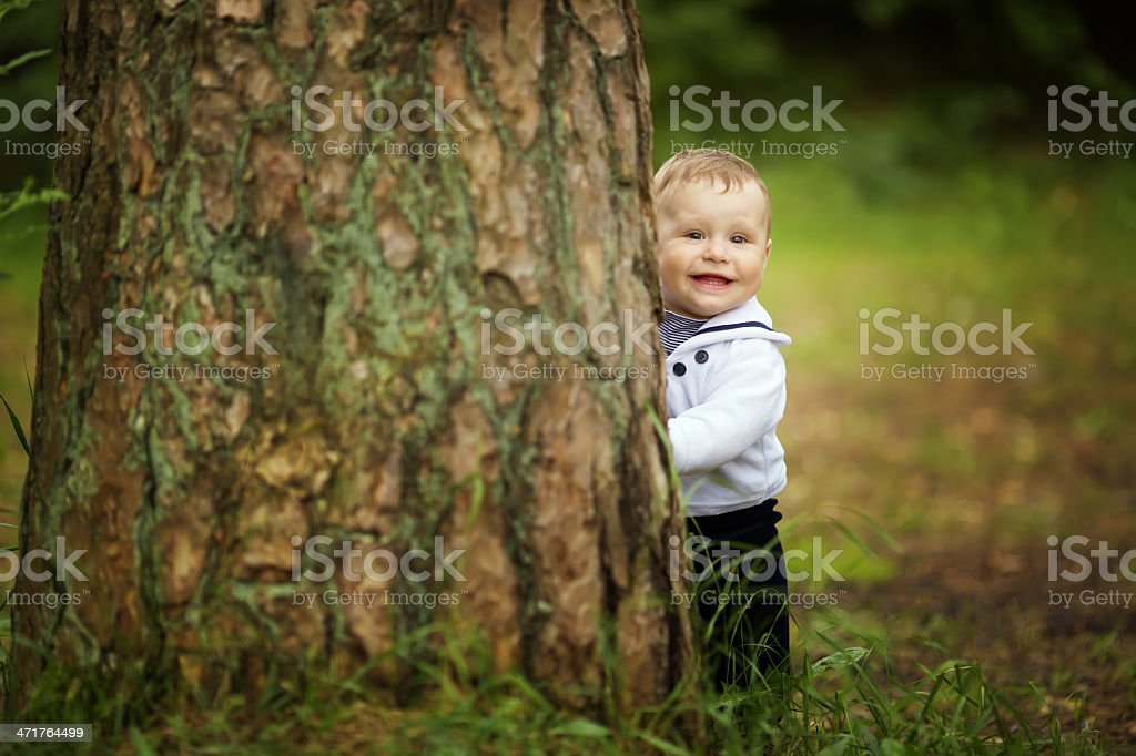 baby hiding behind tree in park royalty-free stock photo