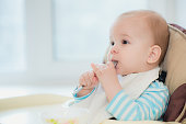 baby holding a spoon in his mouth