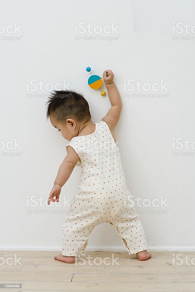 Baby holding a toy near wall stock photo
