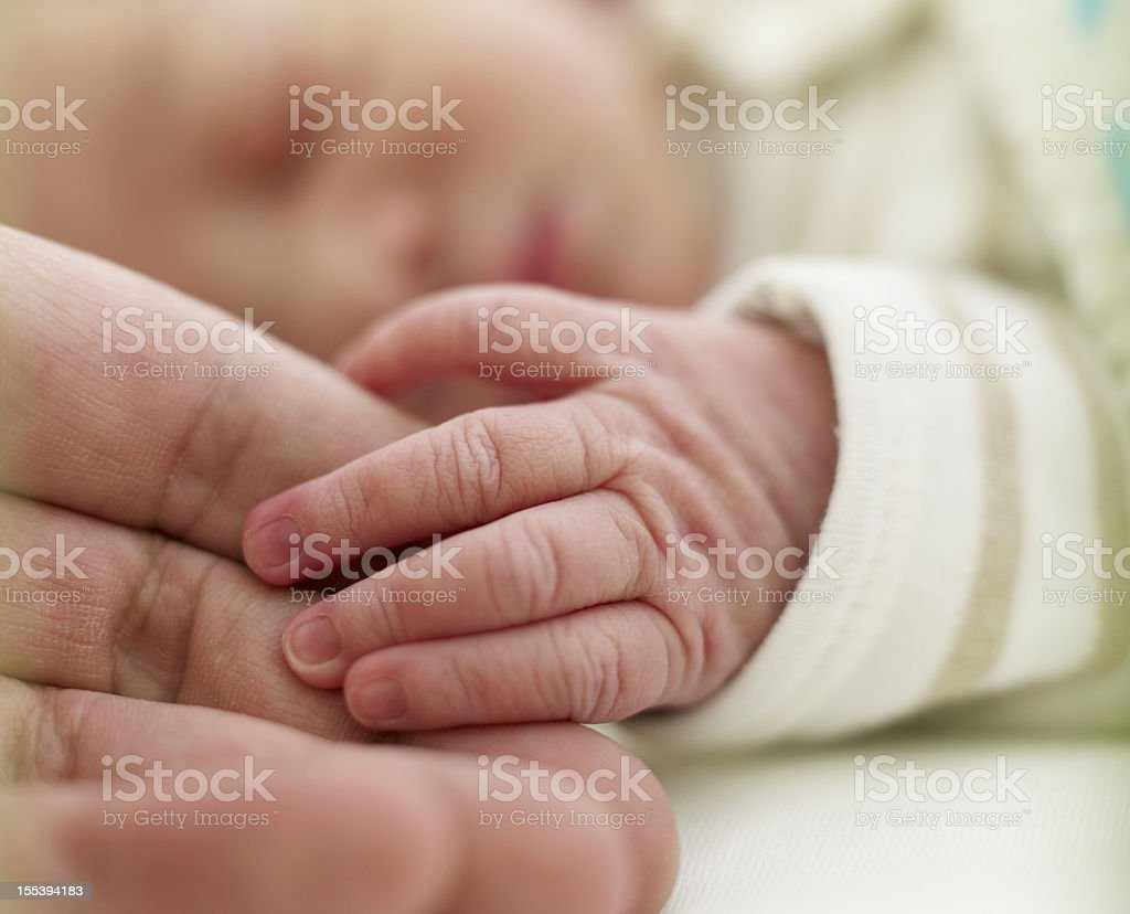 Baby holding adult finger royalty-free stock photo