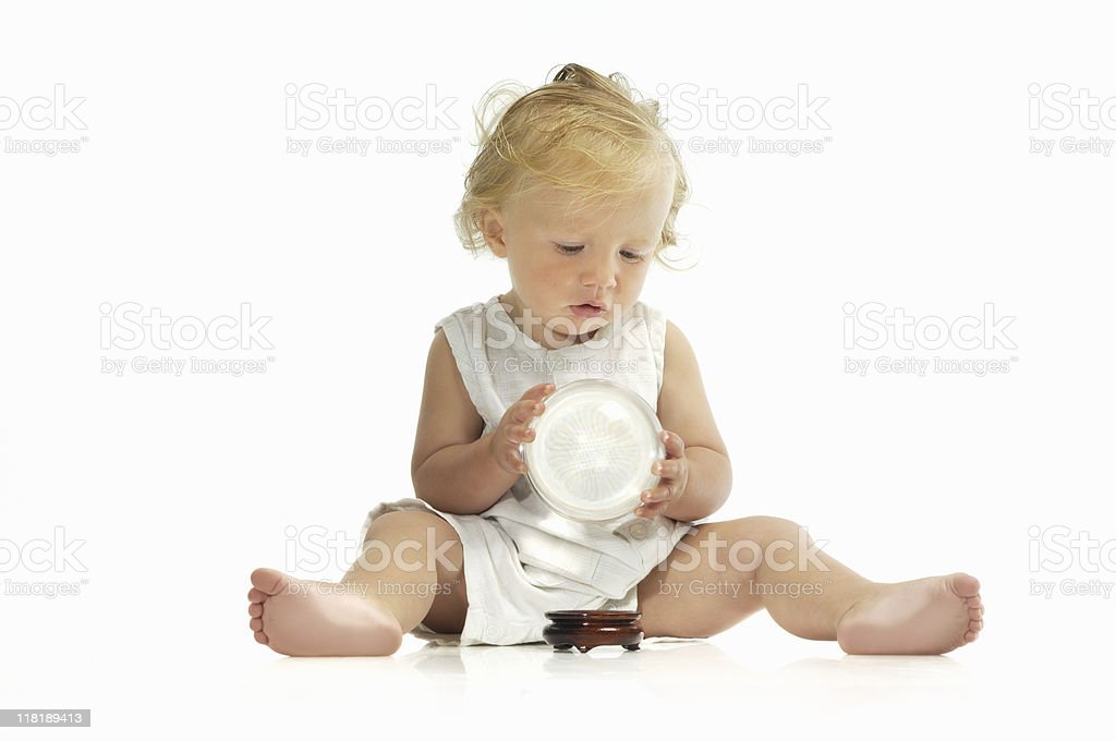 Baby holding and looking into a crystal ball stock photo