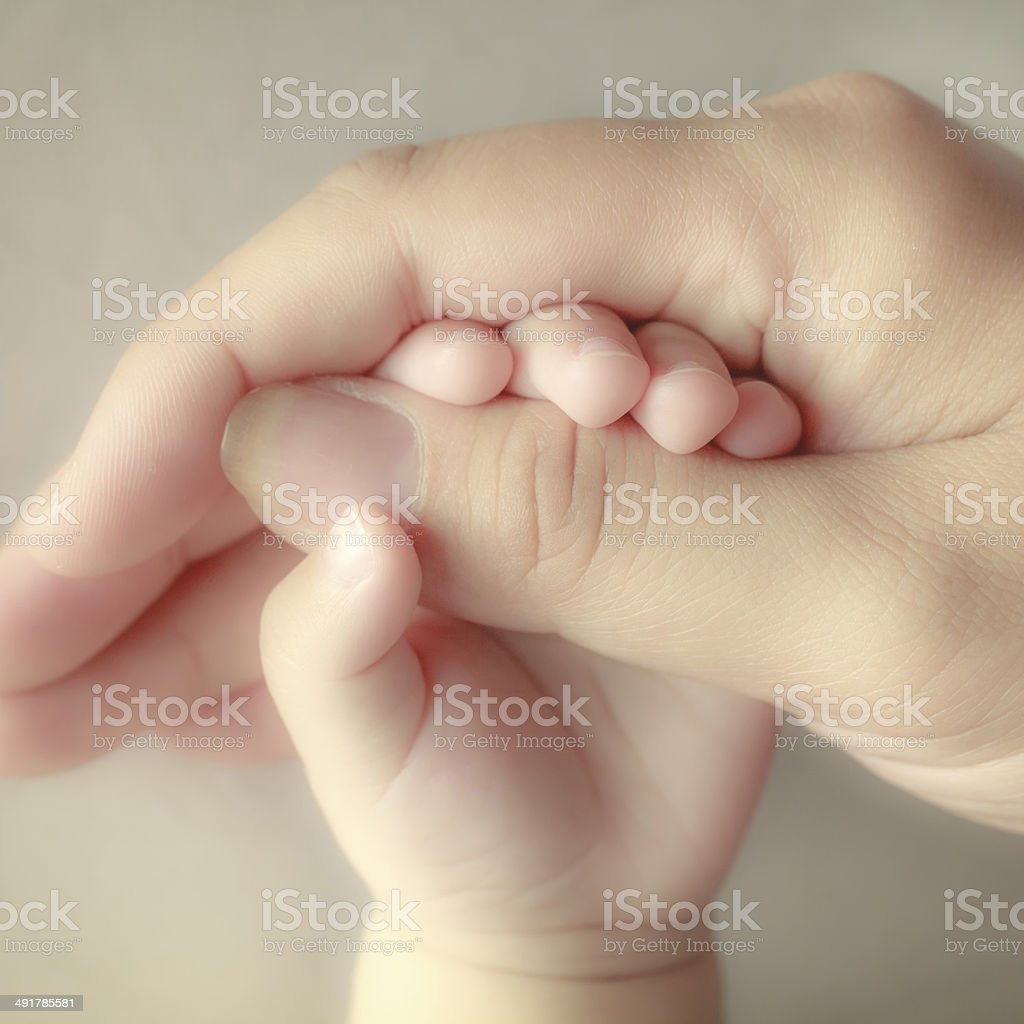 baby holding his mothers finger, selective focus stock photo