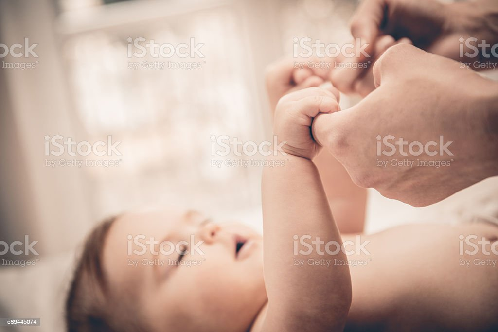 Baby holding mother's hand and finger stock photo