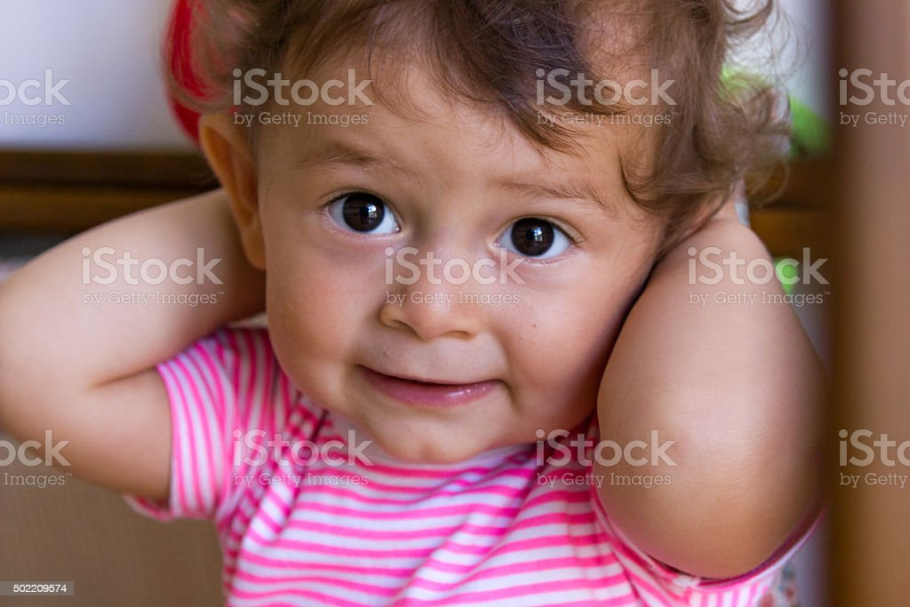 Baby holds hands behind head stock photo