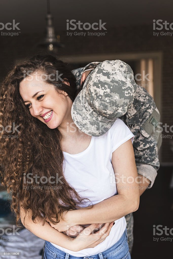 Baby I'm home. Soldier kissing his wife stock photo