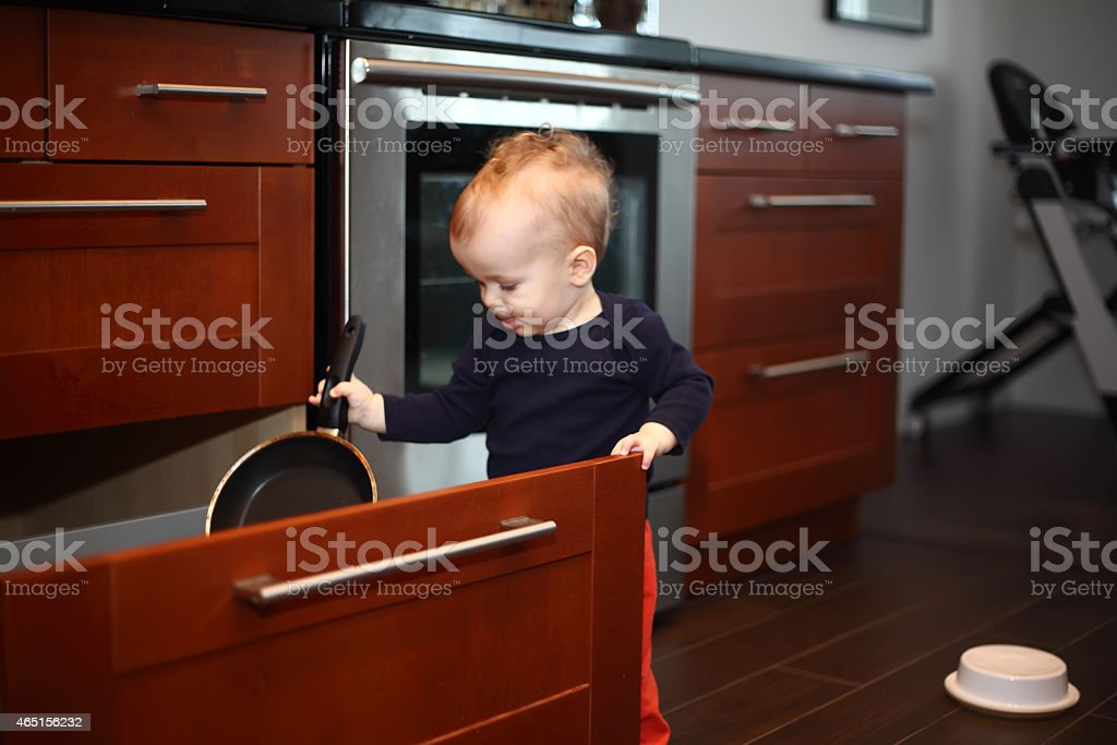 Baby in a luxurious decorated kitchen playing with cookware stock photo