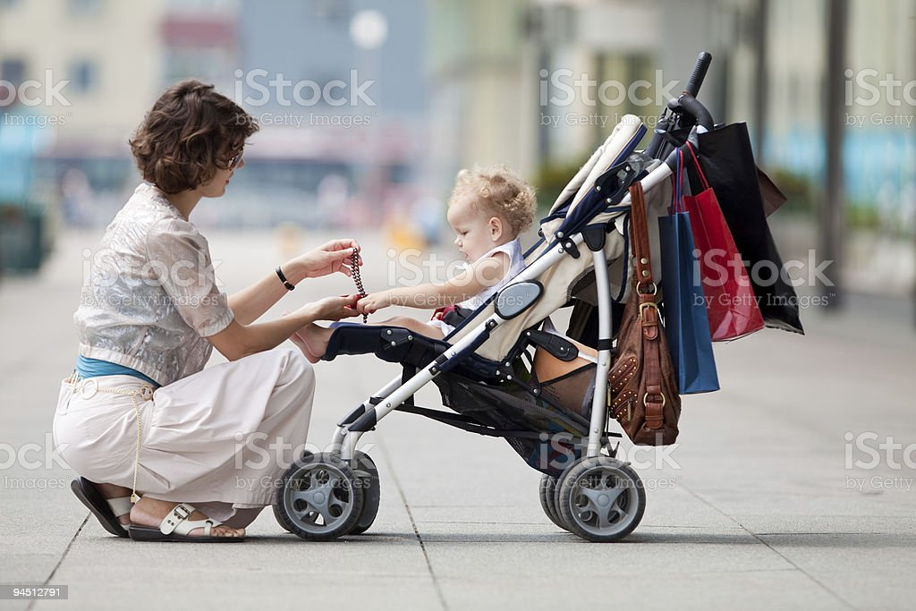 Baby in a stroller while her mother gives her a gift stock photo