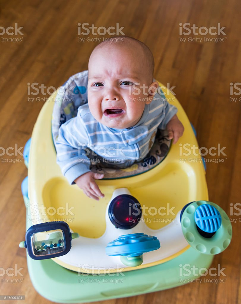 Baby in baby walker crying stock photo