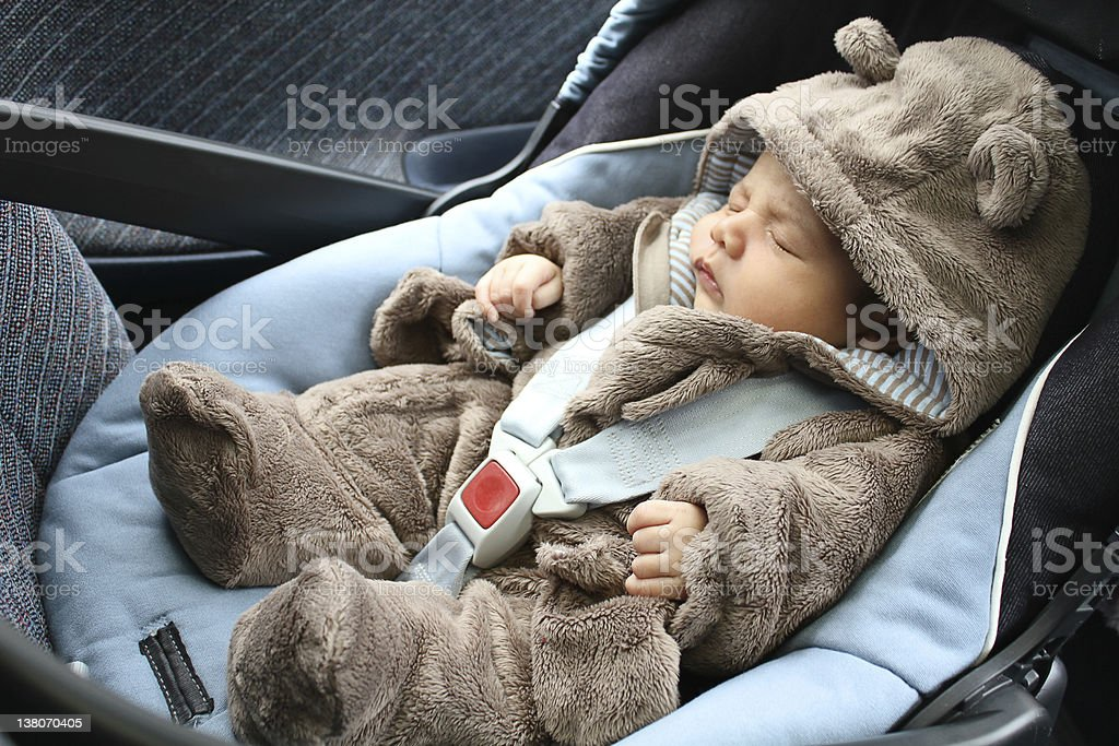 Baby in bear one piece sleeping in a car seat stock photo