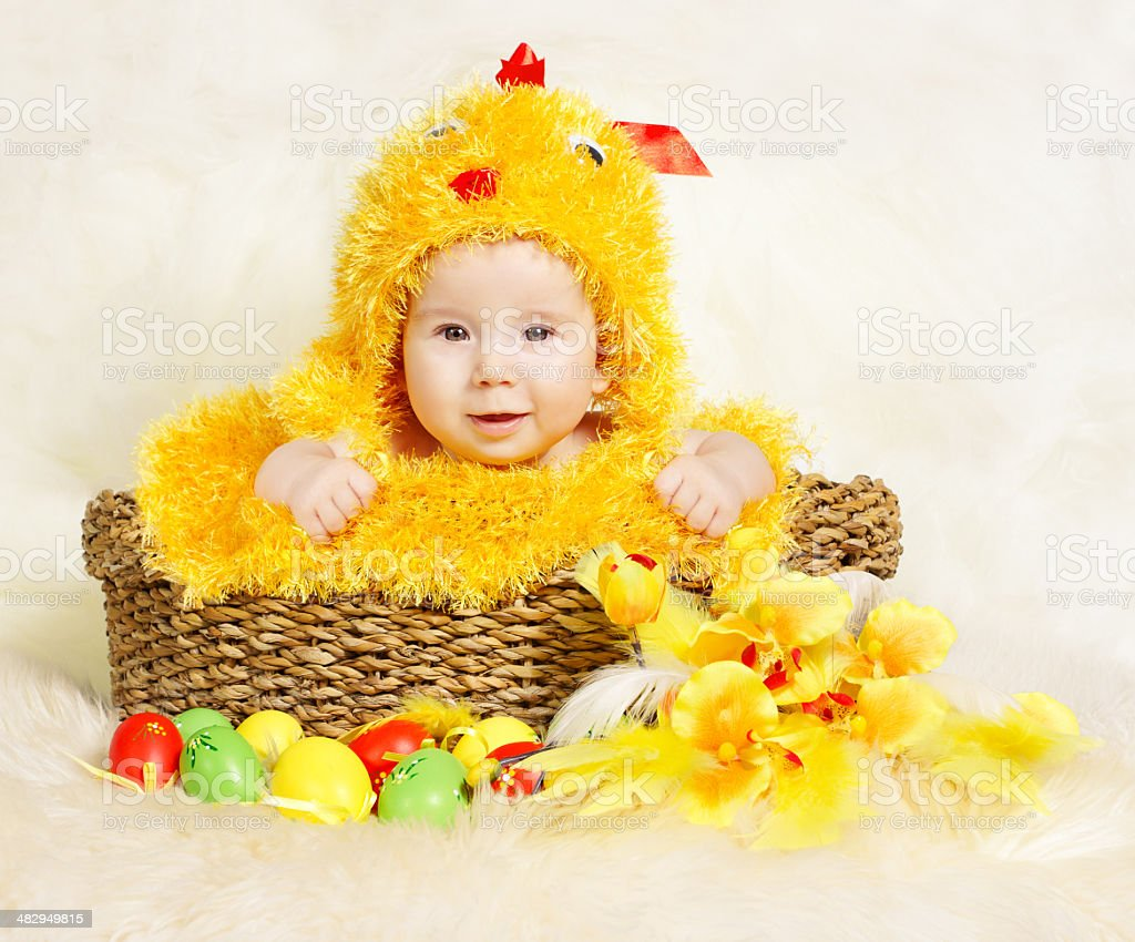 Baby in Easter basket with eggs in chicken costume stock photo