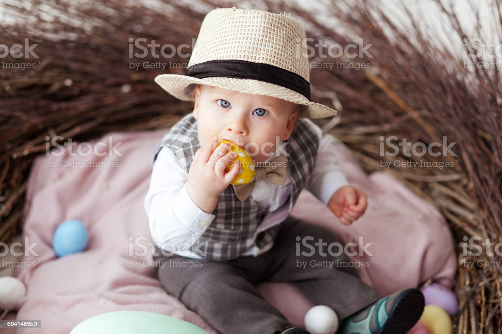Baby in Easter nest with eggs in in a suit and hat. Easter holiday concept: nest with baby stock photo