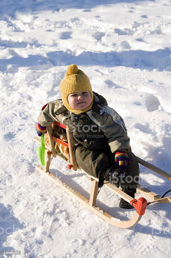 Baby in green coat sitting on sled royalty-free stock photo