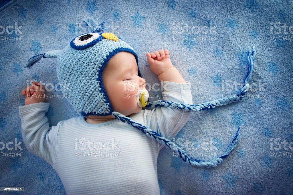 baby in owl hat sleeping stock photo