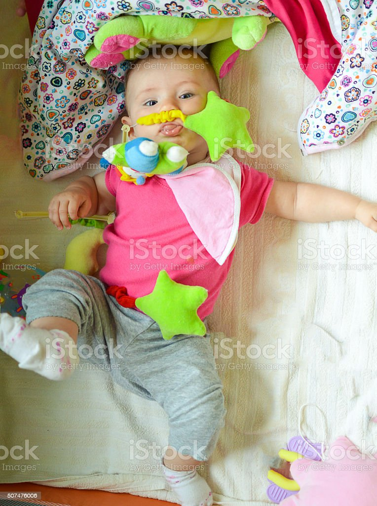 Baby in Playpen with toys stock photo
