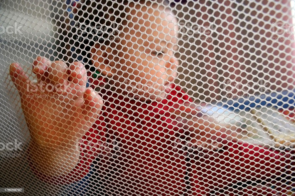 Baby in Portable Crib with Mesh Sides stock photo