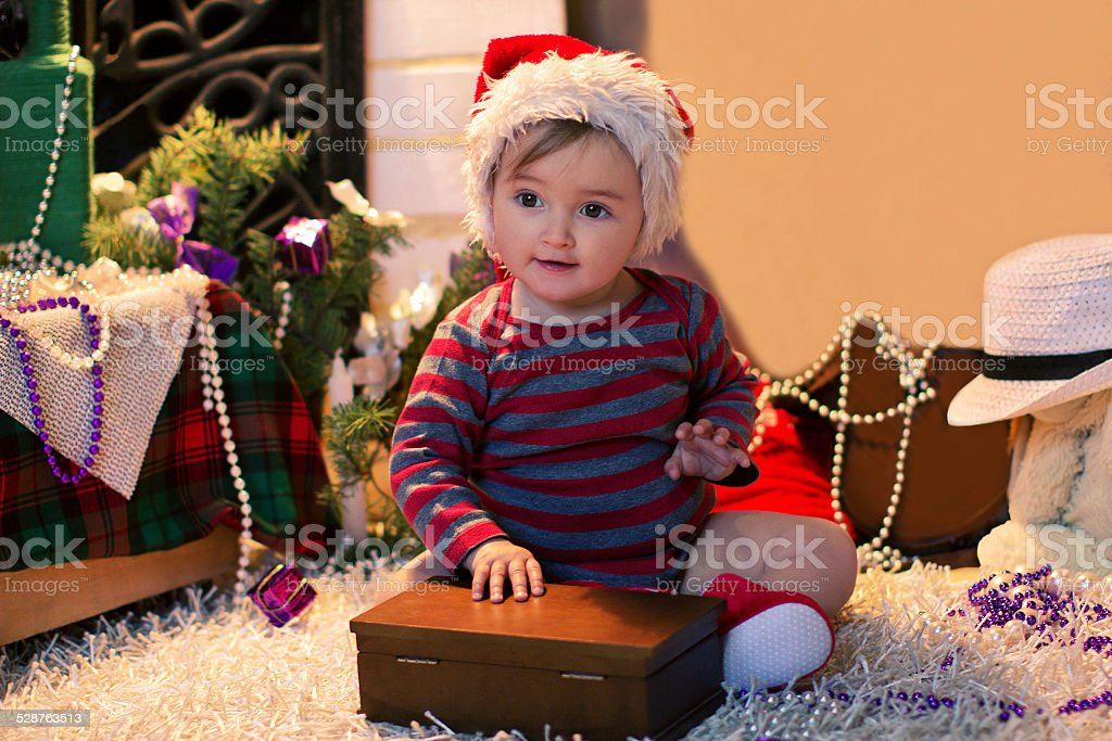 Baby in Santa hat sits and openning a box stock photo