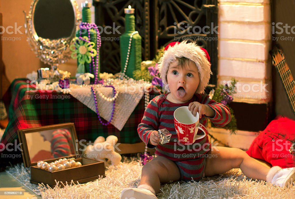baby in Santa hat stuck out her tongue in cap stock photo