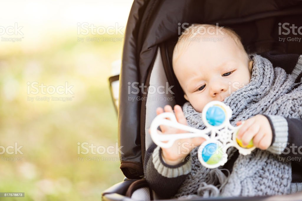 Baby in stroller holding a toy stock photo
